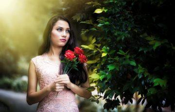 ピンクのワンピースドレスを着た女性が赤いバラを持っている
